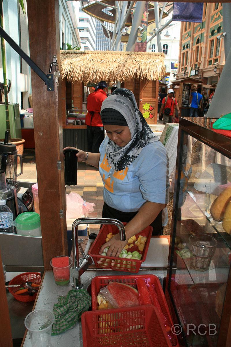 Frau presst frische Säfte an ihrem Stand im Central Market