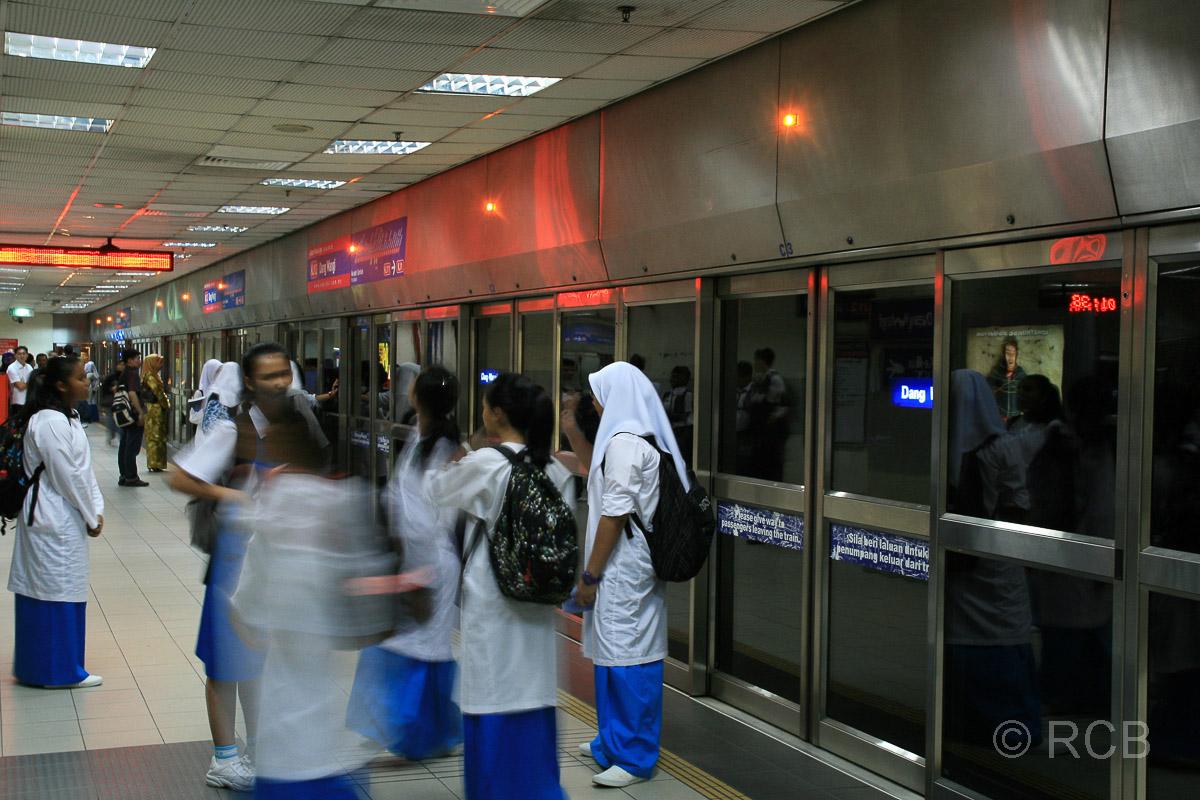 Schulmädchen warten an einer unterirdischen Vorortzug-Haltestelle