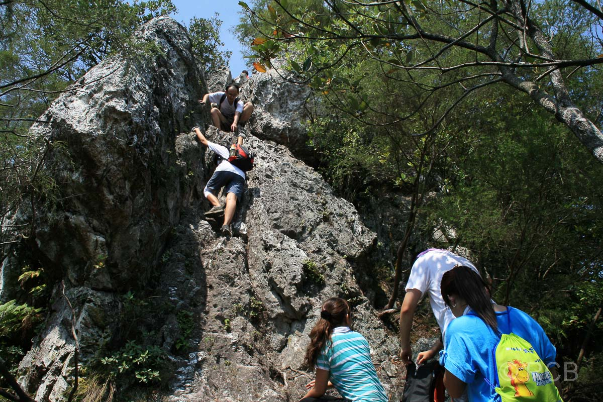 junge Leute erklettern einen Felsen auf dem Bukit Tabor Hike