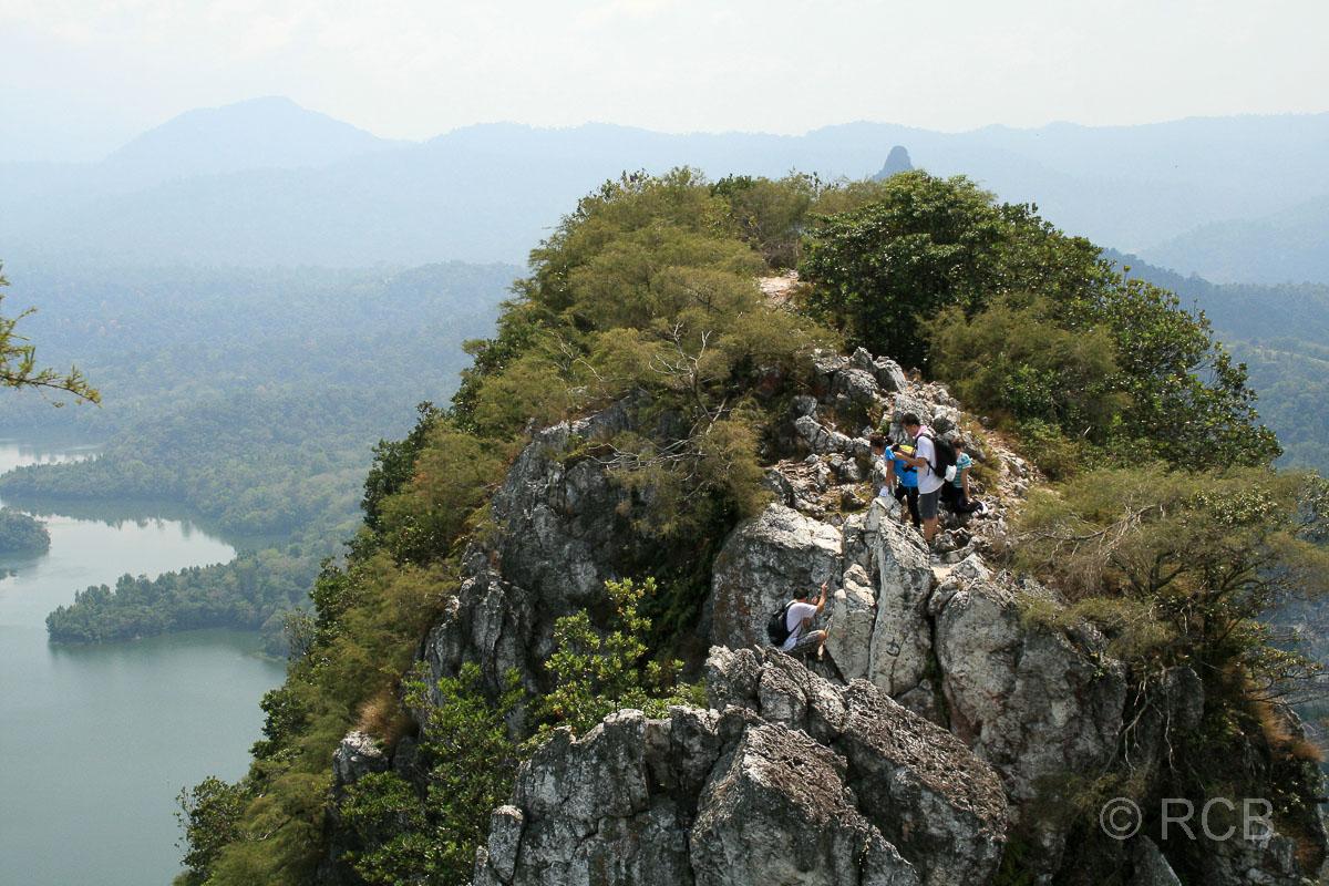 junge Menschen wandern über einen schmalen Felsen auf dem Bukit Tabor Hike auf der Klang Gate Ridge