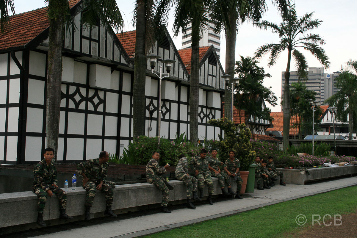 malaysische Soldaten sitzen vor Fachwerkhäusern im englischen Stil auf dem Merdeka Square