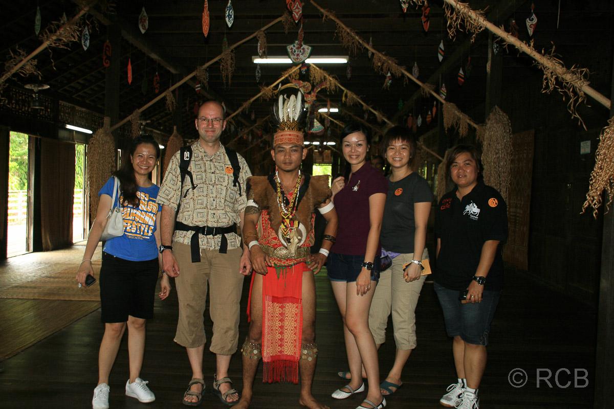Touristen und ein Malaye in Stammestracht lassen sich fotografieren im Sarawak Cultural Village