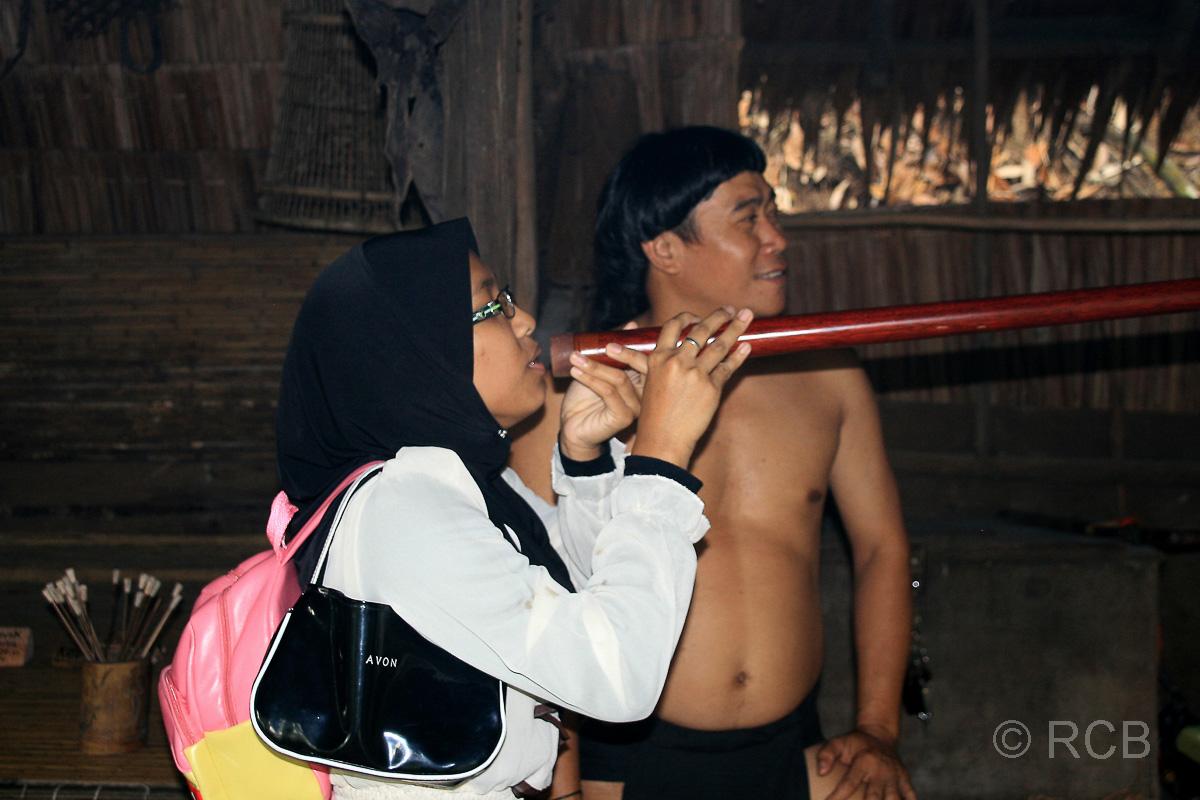 Touristin versucht sich im Blasrohrschießen, Sarawak Cultural Village
