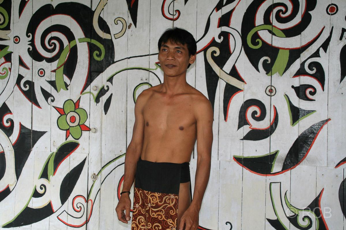 Mann in traditioneller Kleidung vor bemalter Wand, Sarawak Cultural Village