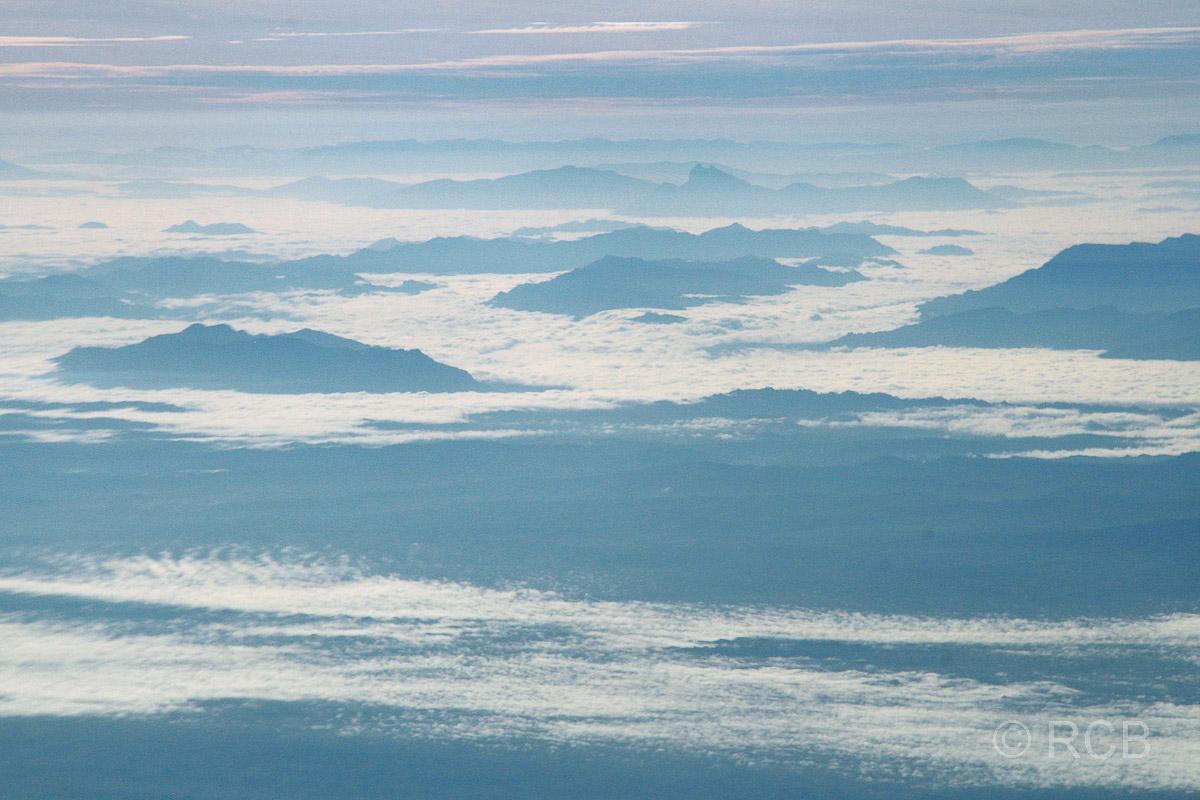 Berge ragen aus den Wolken beim Flug über Sarawak