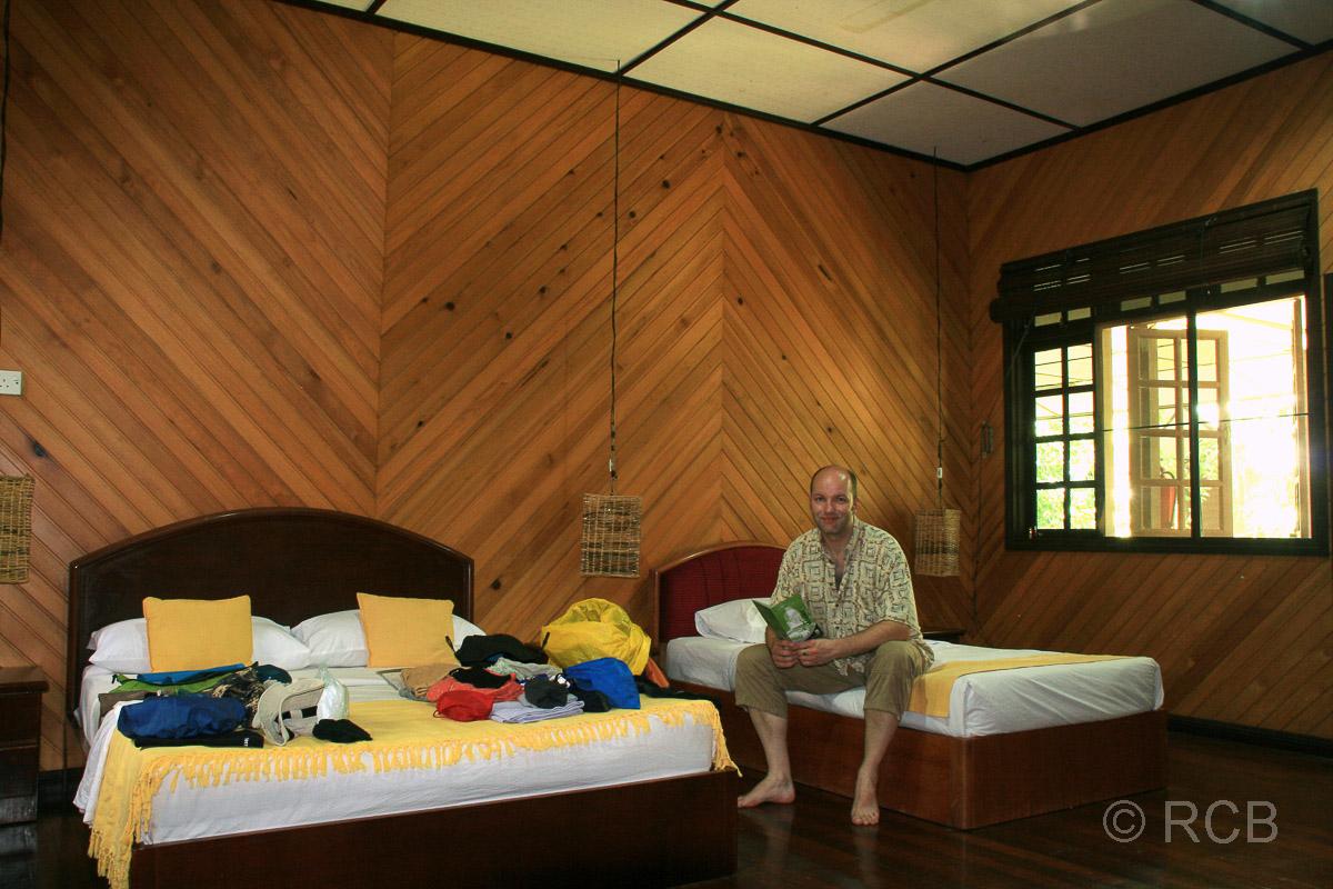 """Mann sitzt auf einem Bett in seinem Gästezimmer in einem umgebauten """"Longhouse"""", Mulu Nationalpark"""