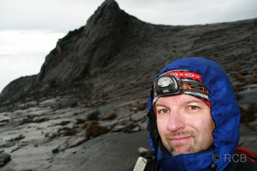 Mann am Gipfelplateau des Mt. Kinabalu mit South Peak