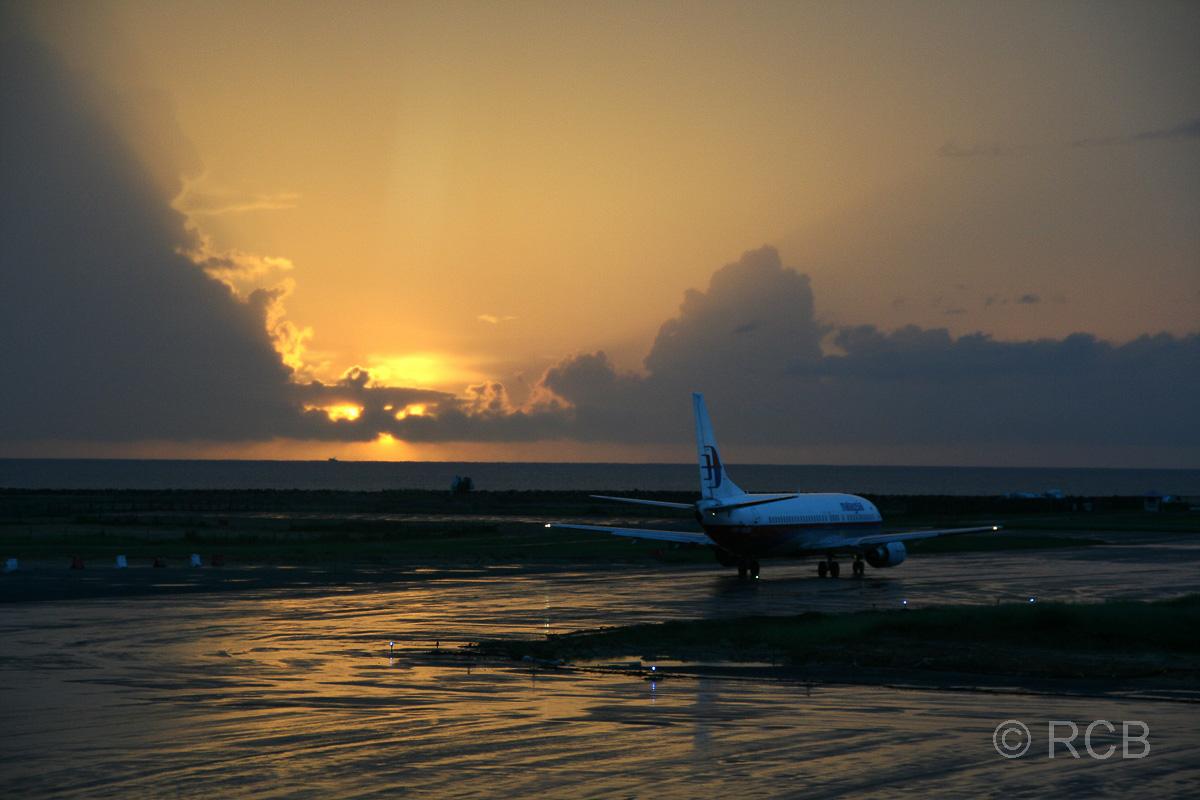 Rollfeld am Flughafen Kota Kinabalu mit einem Flugzeug im Sonnenuntergang